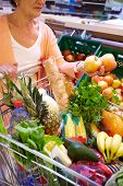 Image of senior woman with fresh vegetables and fruits in cart