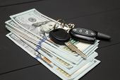Dollars money cash on black background. Heap of money and car key poster