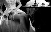 Wedding night preparing garter. Bride undressing and put veil on table. Candle illuminates house. Gi poster