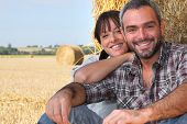 Farming couple sat by hay