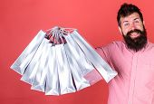 Man With Beard And Mustache Holds Shopping Bags, Red Background. Hipster On Happy Face Is Shopping A poster