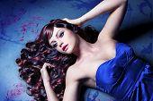 Mädchen mit schönen farbigen lockiges Haar auf einer bemalten Boden wie eine Puppe