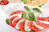 caprese salad and linguine pasta at the back