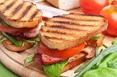 Bacon, lettuce and tomato BLT sandwiches with fresh ingredients at back