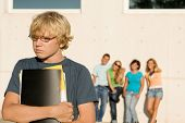 stock photo of bullying  - swot nerd bullied school student by group of bullies - JPG
