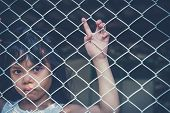 Sad Asian Girl Child Alone In Cage Was Imprisoned Make No Freedom Or Lack Of Freedom poster
