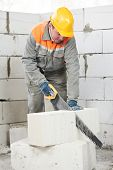 mason construction worker bricklayer sawing off a calcium silicate lime sand brick
