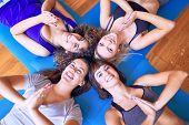 Young beautiful group of sportswomen smiling happy practicing yoga. Lying down doing prayer pose at  poster