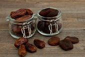 Organic Dried Dates And Dried Apricots, Apricot In Glass Jars Stand On A Wooden Table. Dried Fruits. poster