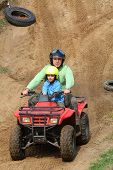 picture of four-wheelers  - Dad with son riding a 4 wheeler on a dirt road - JPG