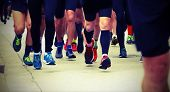 Many Legs Of Fast Runners During A Road Race With Old Toned Effect poster