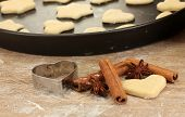 unbaked biscuits on a pan with cutter for biscuits, cinnamon and anise close-up