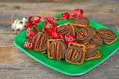 Chocolate Candy Melted On Salty Pretzels With Red Christmas Ribbon And Ornament On Green Square Plat poster