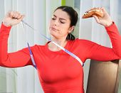 Woman Looks Concerned At A Measuring Tape poster