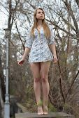 stock photo of leggy  - Barefooted leggy blond woman posing like a statue - JPG