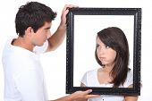 Young couple holding empty picture frame