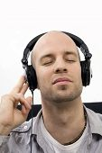 image of bald man  - A young man enjoys music with headphones on - JPG
