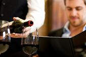 picture of waiter  - Waiter pouring red wine to a man - JPG