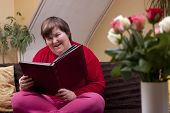 picture of physically handicapped  - Mentally disabled woman is reading a book and smiles - JPG