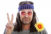 stock photo of hippy  - Unshaven male hippie with long shoulder length hair wearing a headband yellow flower and rose coloured glasses making a peace sign with his fingers head and shoulders portrait isolated on white - JPG