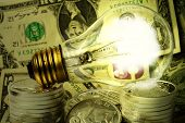 picture of light-bulb  - Light bulb on pile of paper currency and silver coins - JPG