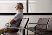 foto of neck brace  - Side view of mature man with neck brace waiting in hospital lobby - JPG