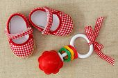 Baby rattle and red shoes on brown background