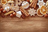 stock photo of biscuits  - Gingerbread cookies and spices over wooden background close up - JPG