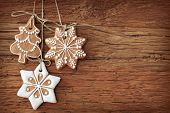 foto of christmas cookie  - Gingerbread cookies hanging over wooden background - JPG