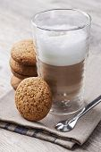 Glass of Latte macchiato coffee with cookies