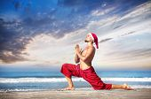 stock photo of namaskar  - Christmas yoga surya namaskar by man in red trousers and Christmas hat on the beach near the ocean in India - JPG