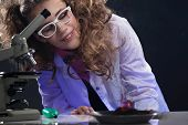 stock photo of physicist  - Smiling young physicist conducting experiment, close-up.  ** Note: Shallow depth of field - JPG