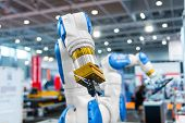 stock photo of machinery  - Robot arm in a factory working for the humans - JPG