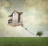 pic of surrealism  - Artistic image representing an house floating in the air tied to a rope to the tree in a surreal vintage background - JPG