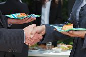 stock photo of office party  - Business handshake during lunch on the open air - JPG