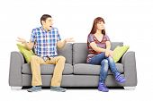 Young couple sitting on a couch during an argument isolated on white background