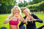 Young happy sporty girls showing heart sign with their hands on a meadow in a park