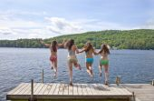 Four Girls Jumping Off A Dock At A Lake