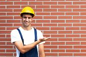 Presenting young worker in front of a brick wall