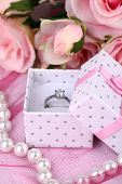Rose and engagement ring on pink cloth