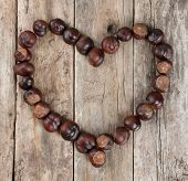 Chestnuts Forming A Heart On A Wooden Background