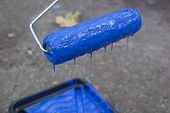 A Paint Roller Dripping Blue Paint Into A Tray