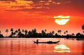 stock photo of alleppey  - Silhouette of boat and fisherman in backwaters at palms and big orange sun background - JPG