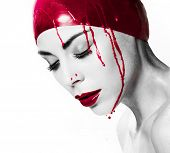 Dramatic artistic portrait of a bleeding woman with closed eyes and a serene expression wearing a re