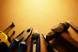 picture of semi-circle  - Sepia toned image of a toolkit for home maintenance with a screwdriver hammer pliers knife tape measure and nails arranged in a semi circle with copy space - JPG