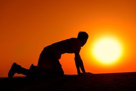 picture of emaciated  - Tired and weaken man on all fours with gold sunset sun disk on background - JPG