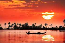 picture of alleppey  - Silhouette of boat and fisherman in backwaters at palms and big orange sun background - JPG