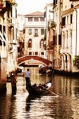 stock photo of gondola  - Gondola traveling down the canals of Venice in Italy - JPG