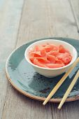 stock photo of zingiber  - Pickled ginger with wooden chopsticks on plate closeup - JPG
