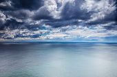 Overcast weather over sea, dark dramatic cloudy sky, dangerous seascape, panoramic landscape